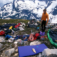 Marshall Balick stands over drying gear on Challenger Arm in the North Pickets, North Cascades National Park.