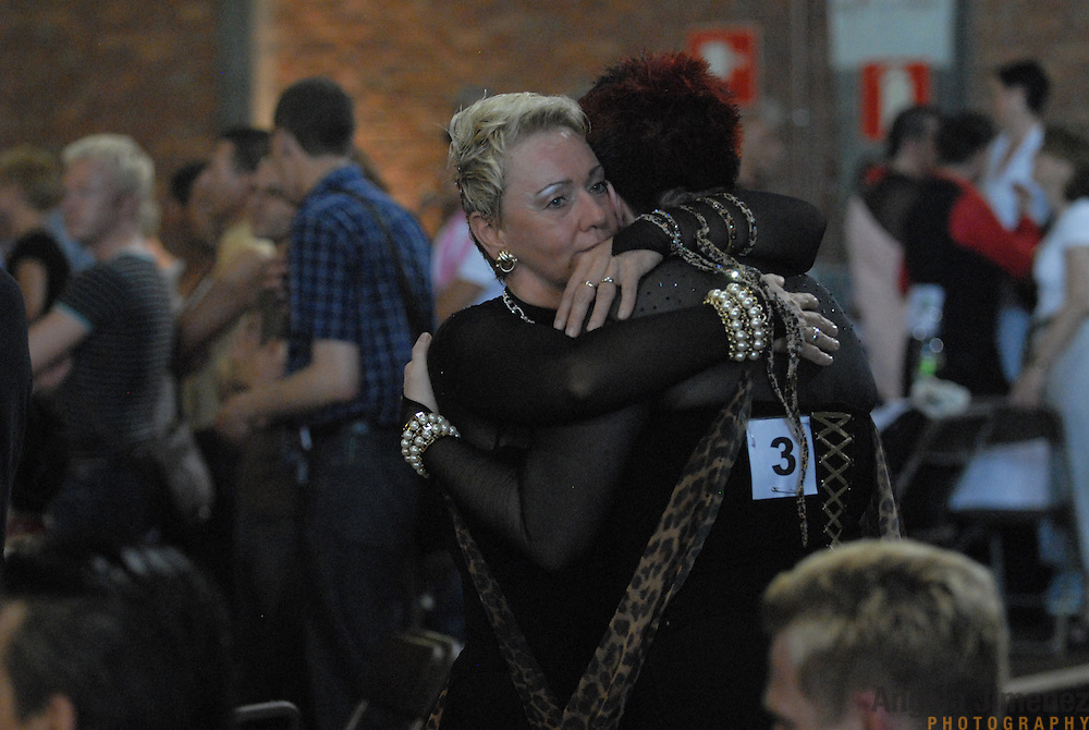 "Andrea Schlinkert, left, comforts dance partner Kerstin Hubner (umlaut on the ""u"" in Hubner), both of Berlin, Germany, after a disappointing performance in the adult women's standard division of  the same-sex ballroom dancing competition during the 2007 Eurogames at the Waagnatie hangar in Antwerp, Belgium on July 13, 2007. ..They were later happily surprised by their third place finish. ..Over 3,000 LGBT athletes competed in 11 sports, including same-sex dance, during the 11th annual European gay sporting event. Same-sex ballroom is a growing sports that has been happening in Europe for over two decades. competes in the same-sex ballroom dancing competition during the 2007 Eurogames at the Waagnatie hangar in Antwerp, Belgium on July 14, 2007. .."