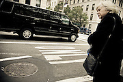 A woman in black waits for the bus while a black van passes near the Metropolitan Museum of Art on the upper east side in Manhattan, New York, USA.
