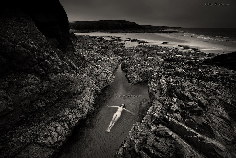 Honourable Mention in 10th Annual Black &amp; White Spider Awards<br /> <br /> &quot;As I child I would spend hours rock-pooling, fascinated by the secret life within its depths, a microcosm of the ocean itself but these days the rock pools are sadly, symptomatically emptier. At low tide on this rugged coast I was therefore truly delighted to discover a woman sensuously enjoying flotation in a breeze blown rockpool, as she considered the universe above&quot;<br /> <br /> Landscape Figures explores the relationship between organic human figures and a notional 'wild landscape. <br /> <br /> &ldquo;Although the nude is vital to the project and integral within the images, the images are not just &lsquo;nudes&rsquo; &ndash; they are landscapes and stories. In a way they are just simple, beautiful, dreamlike visual questions&rdquo;.