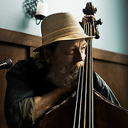 Light falls through an open window upon an acoustic bass player during Sunday brunch.