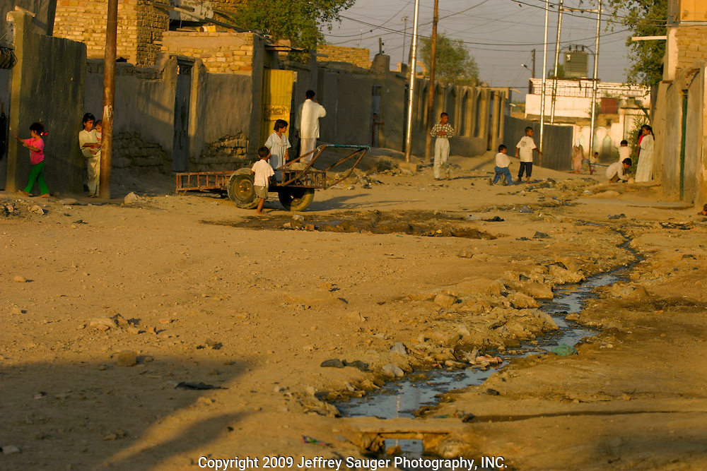 Crude gutters flow with raw sewage as children play in the village Suq ash Shuyukh, about 20 miles southeast of Nasiriyah, Iraq,