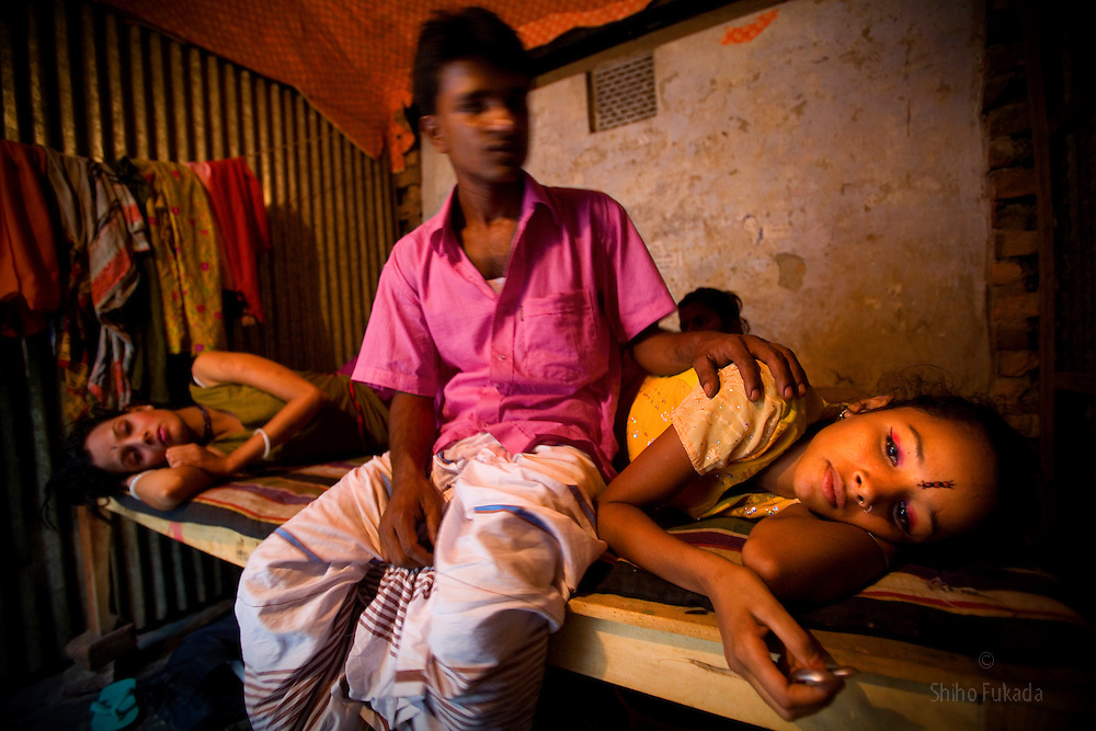 Sex worker sisters Nodi,14, right, and Shetu, 17, left, lie down by a customer at brothel in Tangail, Bangladesh. Nodi run away from home after falling in love with a Hindu boy and ended up in the brothel with her sister. Shetu was sold to a brothel with a false job offer after she run away from an abusive husband.