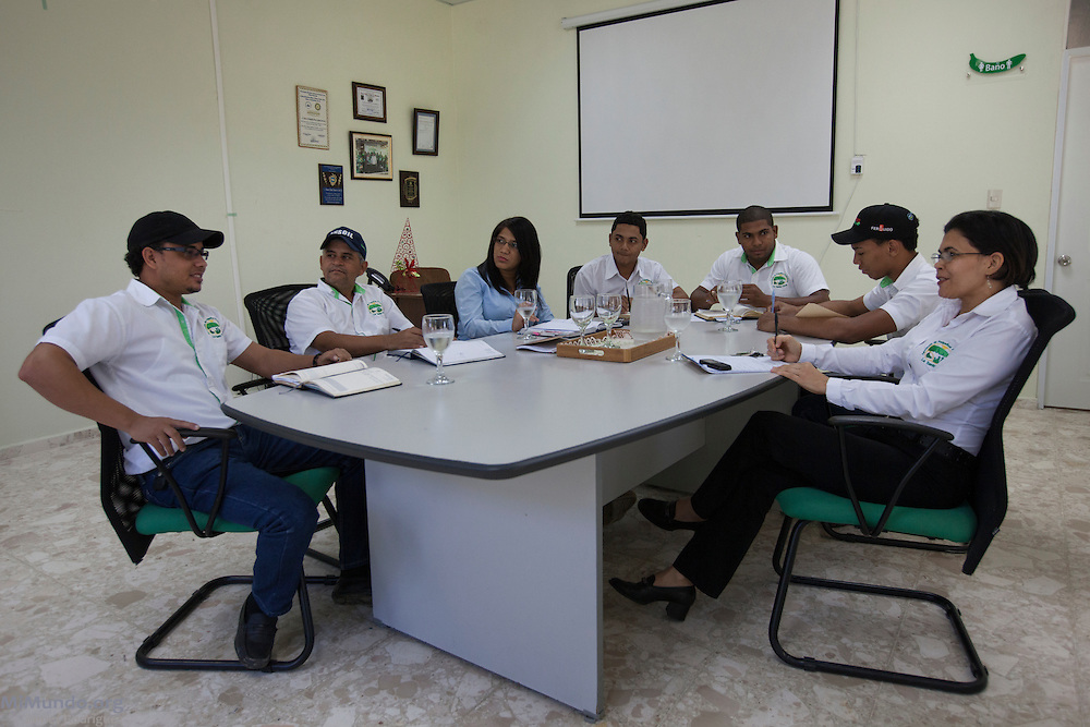 Members of the administration of La Santa Cruz, including Fairtrade certification officer Manuel Martinez (left), hold a meeting at the association's headquarters. La Santa Cruz is an association of small producers in northern Dominican Republic that exports organic bananas certified by the Fairtrade Labelling Organization (FLO). As of December 2014, La Santa Cruz exports 100% of its total production via FLO to England, Germany, France and the Netherlands. Once La Santa Cruz finishes processing its organic certification, it hopes to export 100% of its production as organic bananas via FLO. Mao, Valverde, Dominican Republic. December 9, 2014.