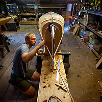 LIVE OAK, FL -- September 30, 2010 -- Boatwright Aaron Wells of Cypress Kayaks LLC, with his dog, Isabella, works on a hand-made wooden canoe in his shop in Live Oak, Fla., on Thursday, September 30, 2010.  (Chip Litherland for Bay Magazine)