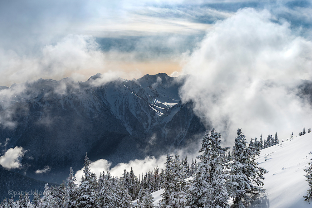 Clouds roll through the valleys between peaks, looking toward one of the glaciers from Hurricane Ridge, ONP.