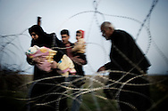 SYRIA, Syria-Turkey Border : Syrian refugees walk through barbwires as they attempt to cross the northwestern part of the Syrian border with neighbouring Turkey, on April 14, 2012, a year after a revolt against President Bashar al-Assad's regime erupted. . ALESSIO ROMENZI