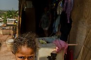 Ana Caroline, nine years old, lives in a makeshift low quality plywood shack in Rosa Leão Occupancy, Isidoro area. According to her mother, Mrs. Maria Amélia, as residents in an irregular occupancy, they haven't regular address and ZIP Code, which hampers to register children in school.