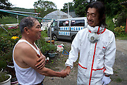 Mr Miura (52) from the NGO Heart Care Rescue,talking to Mr Shinichi Sano (75) who often spends time in his house which he had to evacuate as Iitate village has high levels of radiation.