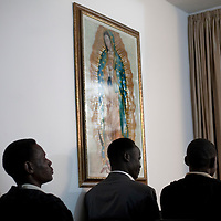 """Sudanese refugees pray during a mass in a house inmprovised into a church  on February 27 2011. The municipality hung 1,500 red flags around the city as a sign of warning and put up hundreds of banners reading: """"Protecting our home, the residents of Eilat are drawing the line on infiltration."""" Eilat Mayor Meir Yitzhak Halevi said that 10 percent of the city's population was currently made up of migrants and that the residents feel that the city has been conquered...Photo by Olivier Fitoussi."""