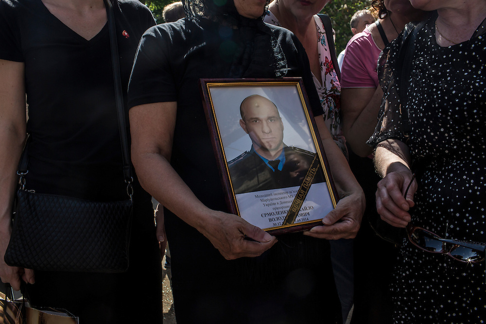 MARIUPOL, UKRAINE - MAY 18: A woman holds a portrait of her son who was killed during violent clashes at a police station last week during a memorial service on May 18, 2014 in Mariupol, Ukraine. A week before presidential elections are scheduled, questions remain whether the eastern regions of Donetsk and Luhansk are stable enough to administer the vote. (Photo by Brendan Hoffman/Getty Images) *** Local Caption ***