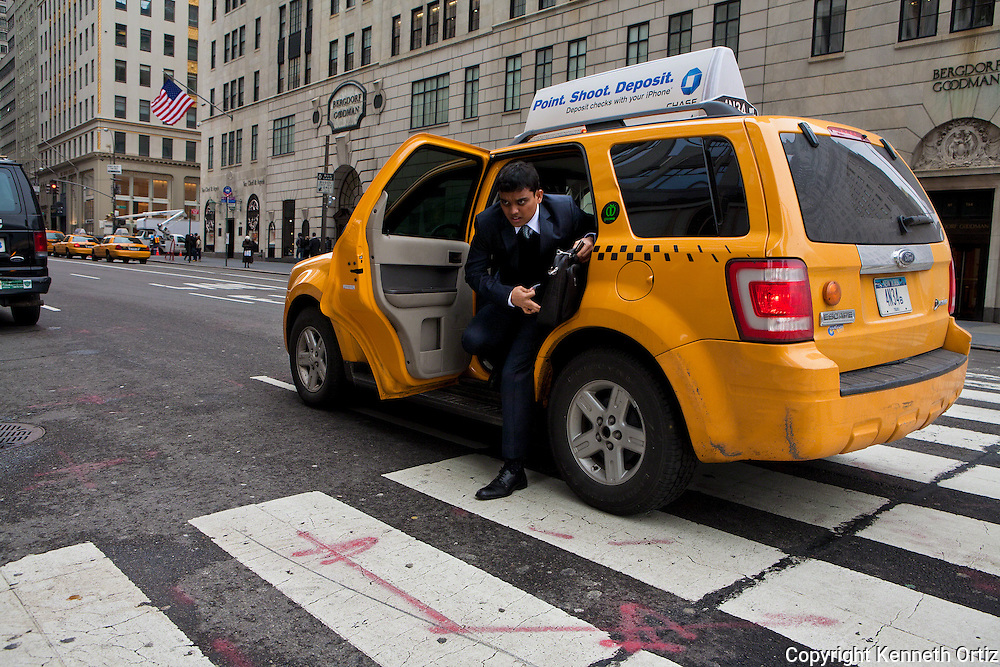 A young man exits from a cab on the corner of 58th Street & 5th Avenue.  In the process of doing so he looks quite harried and stressed. He 's probably late for a meeting.