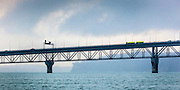 Lime green tanker truck crossing Auckland Harbour bridge, on a rainy day.