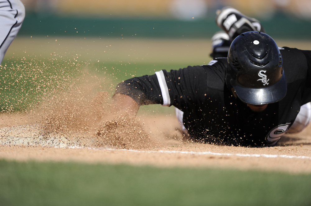 GLENDALE, AZ - MARCH 03:  Eduardo Escobar #62  of the Chicago White Sox dives back safely into first base during the game against the Seattle Mariners on March 03, 2011 at The Ballpark at Camelback Ranch in Glendale, Arizona. The White Sox defeated the Mariners 6-1.  (Photo by Ron Vesely)