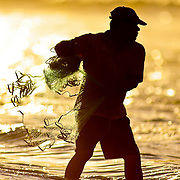 """SHOT 1/12/10 6:04:38 PM - A local fisherman casts a net while fishing along the shoreline in Sayulita, Mexico. Sayulita is a small fishing village about 25 miles north of downtown Puerto Vallarta in the state of Nayarit, Mexico, with a population of approximately 4,000. Known for its consistent river mouth surf break, roving surfers """"discovered"""" Sayulita in the late 60's with the construction of Mexican Highway 200. In recent years, it has become increasingly popular as a holiday and vacation destination, especially with surfing enthusiasts and American and Canadian tourists. (Photo by Marc Piscotty / © 2009)"""