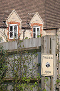 Cotswold stone coloured Neighbourhood watch sign by a new housing development, North Nibley