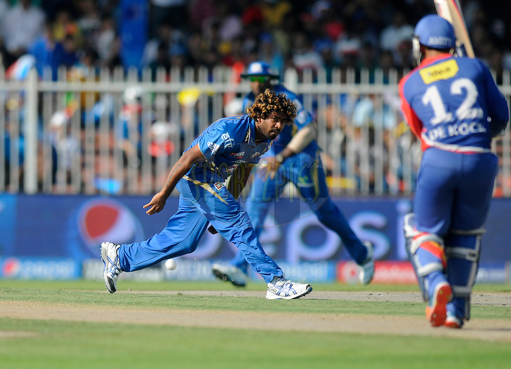 Lasith Malinga of the Mumbai Indians tries to stop a ball of his own bowling during match 16 of the Pepsi Indian Premier League 2014 between the Delhi Daredevils and the Mumbai Indians held at the Sharjah Cricket Stadium, Sharjah, United Arab Emirates on the 27th April 2014<br /> <br /> Photo by Pal Pillai / IPL / SPORTZPICS