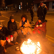 Protestors with the Black Lives Matter movement huddle around fires as they gather for a night of community and protest outside the Minneapolis Police Department 4th precinct headquarters on Thursday, November 19, 2015 in Minneapolis, Minnesota. <br /> <br /> A more mellow and festive atmosphere, with a smaller police presence, prevailed after Wednesday evening's tear gas clashes between police and protesters. <br /> <br /> Protests and an encampment at the site have been ongoing since the police shooting of 24-year-old Jamar Clark by Minneapolis Police on Sunday, November 15. <br /> <br /> <br /> Photo by Angela Jimenez for Minnesota Public Radio www.angelajimenezphotography.com