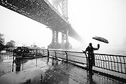A girl with an umbrella by the Manhattan Bridge during a snow storm in DUMBO, Brooklyn
