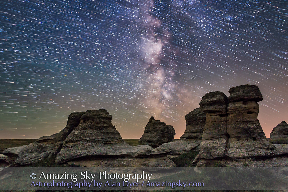 The stars trailing in motion over the sandstone formations of Writing-on-Stone Provincial Park in southern Alberta, on July 31, 2016. The foreground is illuminated only by natural starlight and sky glow; no artificial illumination employed to &ldquo;light paint&rdquo; the foreground. This was at New Moon, so there was no moonlight. <br /> <br /> While this is a highly-manipulated image, it is a composite of exposures all taken at the same shoot with the same fixed camera. The ground did not come from some other night or shooting session. <br /> <br /> This is a stack of 100 images, all 30-second exposures at f/2 and ISO 4000, to create the star trails, with the last image blurred to out a glow around the stars at the end point of the trails and to being out the Milky Way. The ground is from a single 6.5-minute exposure taken at the end of the sequence at f/4 and ISO 1600 for more depth of field, less noise, and more detail in the foreground. Star trail stacking with Advanced Stacker Plus actions using Comet effect. Compositing in Photoshop. Other layers not seen here are included in the master image to compare the difference in the foreground, between a single short exposure, a single long exposure at lower ISO, and a stack of 8 exposures averaged, to compare noise and detail in demos. A single sky layer is also included. An LENR dark frame was applied to the 6.5-minute foreground image.