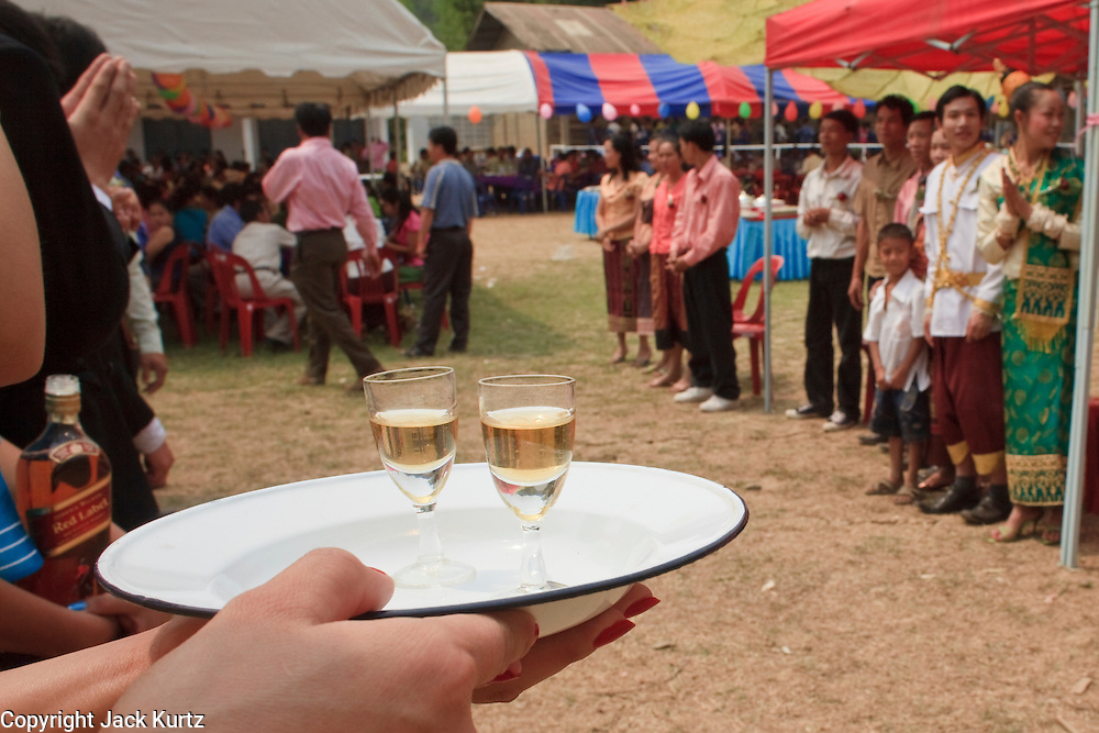 Mar. 14, 2009 -- LUANG PRABANG, LAOS: A hostess serves Johnie Walker Scotch to guests arriving at a wedding reception north of Luang Prabang, Laos.  Photo by Jack Kurtz / ZUMA Press