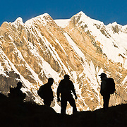 "The silhouettes of trekkers stand against the impressive mountain face of Fang (or Baraha Shikhar 25,088 feet / 7647 meters), in the Annapurna Range of Nepal. Published on the front cover of ""Light Travel: Photography on the Go"" by Tom Dempsey 2009, 2010. Published September 29, 2016 in Amateur Photographer magazine, London, UK, ""Expert guide to silhouette photography"": http://www.amateurphotographer.co.uk/technique/camera_skills/silhouette-photography-taking-shape-96009"