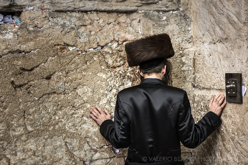 A Haredim in Shabbat clothes prays inside the covered section of the western wall. Traditional bekishe coat, a long coat usually made of black silk, is worn mainly on Shabbat. The fur hat, Shtreimel, is worn by married haredi Jewish men on Jewish holidays. The piece of papers into the crevices of the wall contain written prayers to God left as wishes by Jewish believers. Over a million notes are placed each year. The notes are collected twice a year and buried on the nearby Mount of Olives.