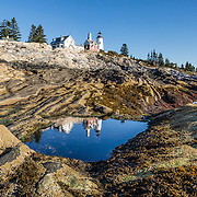 A unique landscape of beautifully striped bedrock descends from Pemaquid Light to the Atlantic Ocean. Pemaquid Point Lighthouse was built in 1835 and commemorated on Maine's state quarter (released 2003). Visit Lighthouse Park at the tip of Pemaquid Neck in New Harbor, near Bristol, Lincoln County, Maine, USA. From Damariscotta on bustling US Highway 1, drive 15 miles south on Maine Route 130 to the park. The keeper's house (built 1857) is now the Fishermen's Museum at Pemaquid. Geologic history: Silurian Period sediments laid down 430 million years ago were metamorphosed underground into a gneiss 360-415 million years ago, and intruded by molten rock which cooled slowly, creating the park's exposed metamorphic gray rocks with dikes of harder, white igneous rock. Underground heat and pressure tortured and folded the rock layers into the striking patterns that are now pounded and polished by the sea and rough weather. The panorama was stitched from 3 overlapping photos.