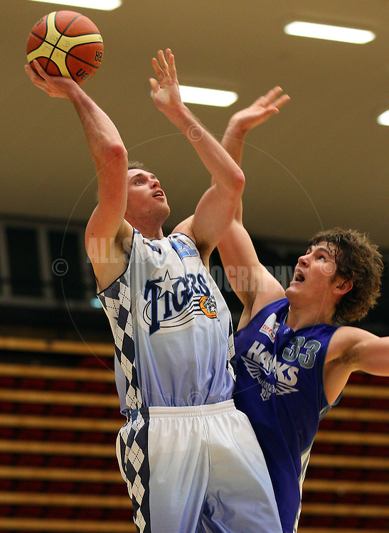 PERTH, AUSTRALIA - JULY 16: Troy Thomson of the Tigers shoots overBen Purser of the Hawks during the week 18 SBL game between the Perry Lakes Hawks and the Willetton TIgers at The State Basketball Center on July 16, 2011 in Perth, Australia.  (Photo by Paul Kane/Allsports Photography)