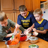 Zachary Frantzen (C) heaps brothers Trent (L) and Joshua (R) prepare dinner in Longmont, Colorado July 19, 2010.  Zachary, 10, is in the Shapedown Program which is part of the child and teen weight management program at The Children's Hospital in Aurora. REUTERS/Rick Wilking (UNITED STATES)