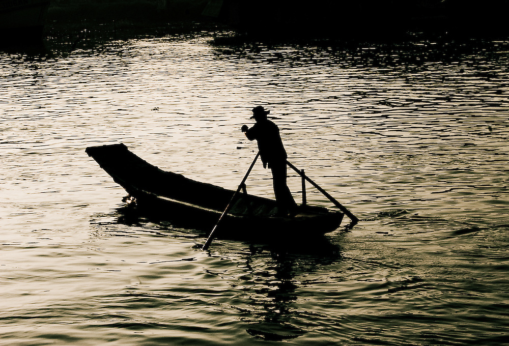 A man paddles his boat through the port of Rach Gia, Vietnam, Southeast Asia.