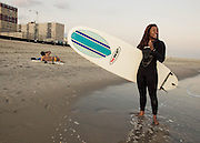 A female surfer poses with her surfboard while a man talks on his phone on the beach, Rockaway Beach, Queens, NY.