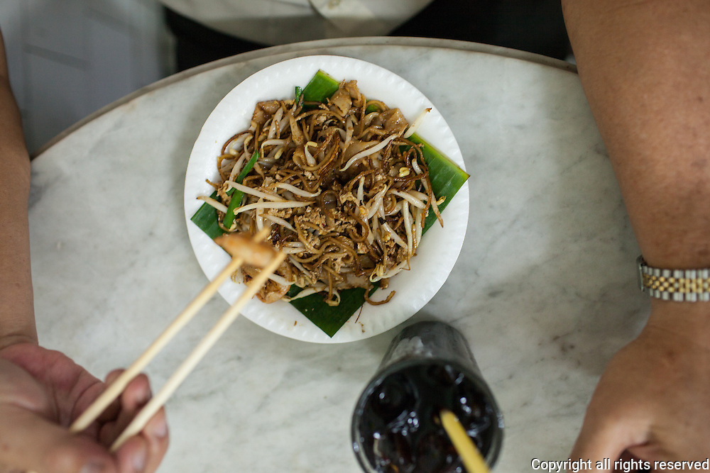 Char koay teow, fried rice noodles with shrimp an dbean sprouts served with iced black coffee. Ipoh, Malaysia
