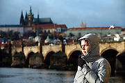 """SHOT 11/21/08 7:43:17 AM -  Portrait of Margaret Ebeling in front of the Charles Bridge and Prague Castle in Prague, Czech Republic. Prague is the capital and largest city of the Czech Republic. Its official name is Hlavní m?sto Praha, meaning Prague, the Capital City. Situated on the River Vltava in central Bohemia, Prague has been the political, cultural, and economic centre of the Czech state for over 1100 years. The city proper is home to more than 1.2 million people, while its metropolitan area is estimated to have a population of over 1.9 million. Since 1992, the extensive historic centre of Prague has been included in the UNESCO list of World Heritage Sites. According to Guinness World Records, Prague Castle is the largest ancient castle in the world. Nicknames for Prague have included """"the mother of cities"""", """"city of a hundred spires"""" and """"the golden city"""". Since the fall of the Iron Curtain, Prague has become one of Europe's (and the world's) most popular tourist destinations. It is the sixth most-visited European city after London, Paris, Rome, Madrid and Berlin. Prague suffered considerably less damage during World War II than some other major cities in the region, allowing most of its historic architecture to stay true to form. It contains one of the world's most pristine and varied collections of architecture, from Art Nouveau to Baroque, Renaissance, Cubist, Gothic, Neo-Classical and ultra-modern..(Photo by Marc Piscotty / © 2008)"""