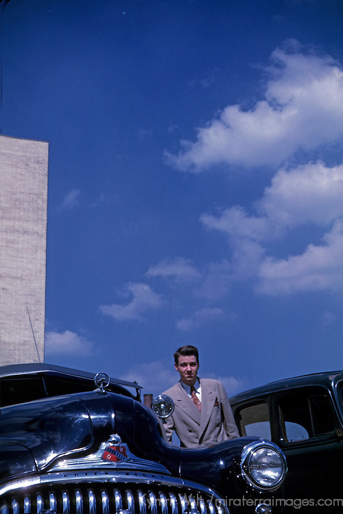 USA.  Young man stands alongside a classic Buick Eight. late 1940's. Private collection.