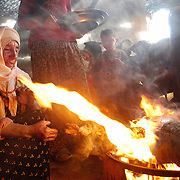 """Cooking distinctive """"Beritan"""" kebab--hunks of meat wrapped is a combustible skin of fat--for lunch. Tribe members who continue to live as nomads are quick to point out when tasks, from pitching tents to milking sheep, are done """"the Beritan way""""."""