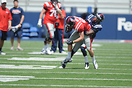 JohnRatliff (88) is tackled by Carlos Davis (20) at Ole Miss' Grove Bowl at Vaught-Hemingway Stadium in Oxford, Miss. on Saturday, April 13, 2013.