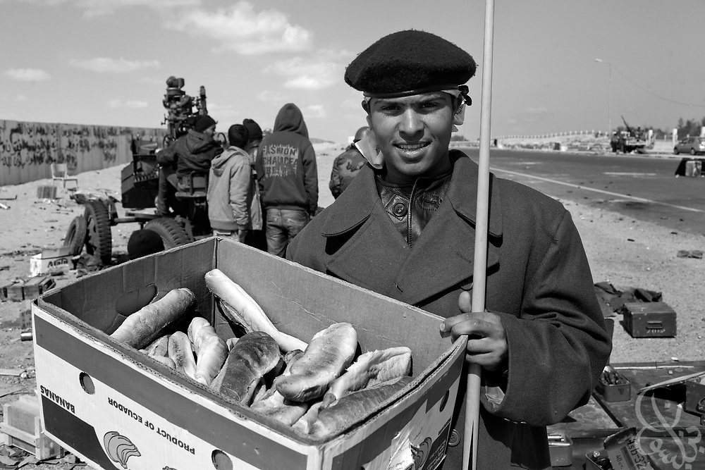 A Libyan rebel fighter passes out fresh loaves of bread March 08, 2011 at a checkpoint in Ras Lanouf, Libya. For more than 2 weeks rebels in Eastern Libya have been battling pro-Qadaffi forces, seeking to topple the nearly 42 year old dictatorship of Col Moammar el-Qadaffi.
