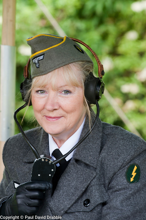 reenactor dressed as German army female signals auxiliary (Nachrichtenheflrennin des heeres) also nicknamed Blitzm&auml;dchen or lightening girls because of the signals insignia on their uniforms.<br />