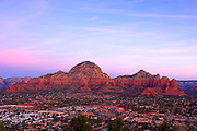 View of Sedona, Arizona at sunrise from airport overlook. Red rock formation lighted by sunrise rises behind city.