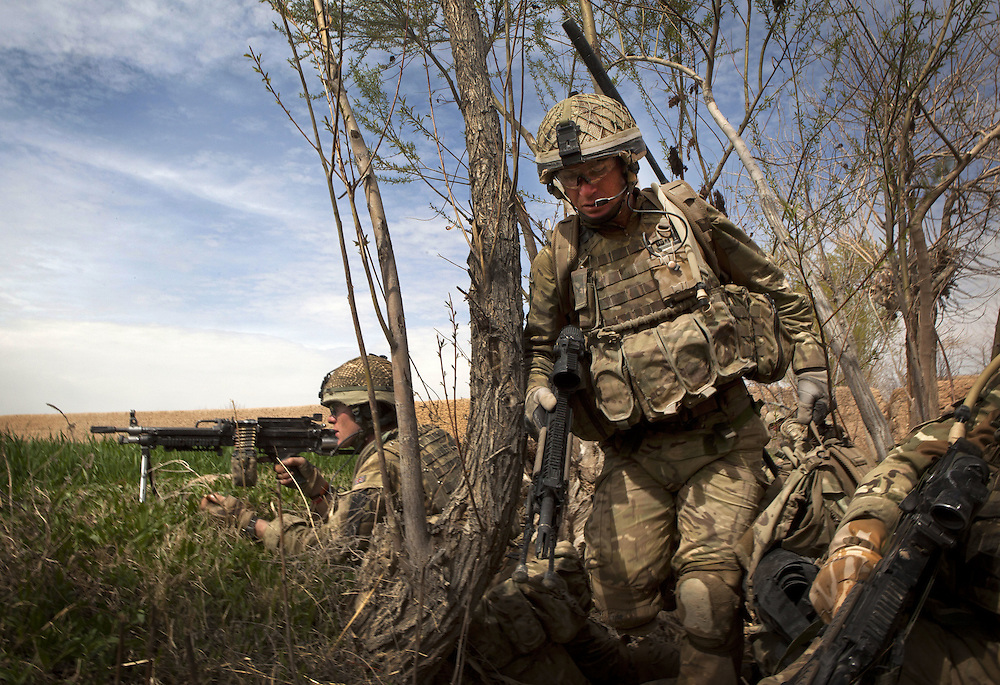 British soldiers of 3PARA use irrigation ditches and waterways for cover as they take up defensive positions during a patrol in Nad Ali, Hemand Province, Afghanistan on the 11th of March 2011.