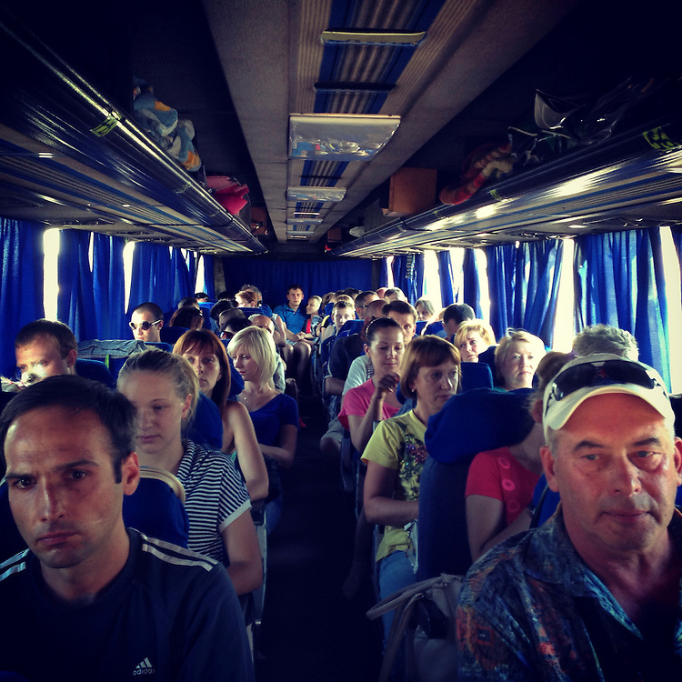 Refugees fleeing fighting in nearby Horlivka take a bus to the Crimean city of Simferopol on Sunday, July 27, 2014 in Makiivka, Ukraine.