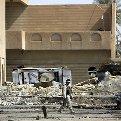 Soldiers guard the Jordanian embassy, where a car bomb exploded in front of it the day before, killing 11 people, Baghdad, Iraq, Aug. 8, 2003.