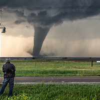 Scientist and Engineer Tim Marshall observes a tornado near Dodge City, Kansas, while taking part in Project TWIRL, a scientific mission to place atmospheric measurement probes in the path of a tornado that is being actively scanned by close-range radar.