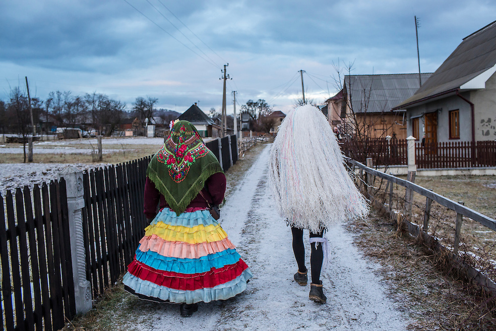 Grygory Pleshka, 28, left, and Georgii Istratii, 26, wearing women's costumes, celebrate the Malanka Festival on Thursday, January 14, 2016 in Krasnoilsk, Ukraine. The annual celebrations, which consist of costumed villagers going in a group from house to house singing, playing music, and performing skits, began the previous sundown, went all night, and will last until evening. According to tradition, married men may only participate in Malanka while wearing a mask.
