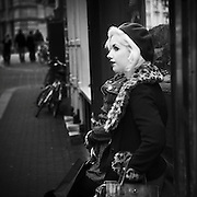 Young stylishly dressed blonde woman standing in front of a shop window in Amsterdam