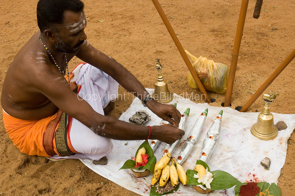 Udappuwa festival. A priest prepares the temporary shrine outside the Mariamman Kovil in the north of the village. The Four Guardian deities will begin their dance from here before proceeding to the Vishnu Kovil in the south of the village.