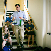 09/03/2013 - Medford/Somerville, Mass. - Students look on as Assistant Professor in Mechanical Engineering Jeff Guasto carries a beaker and flask of unidentified liquids down the stairs of Anderson Hall on Sept. 3, 2013. (Kelvin Ma/Tufts University)