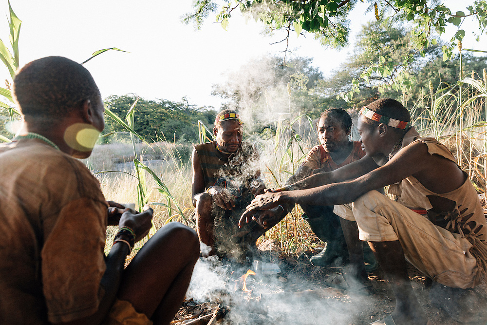Male members of the Hadza tribe sit around in the morning many smoking tobacco or hashish before preparing and mending arrows, testing bows and heading out to hunt. Yaeda valley, Northern Tanzania. Photo by Greg Funnell, March 2016.