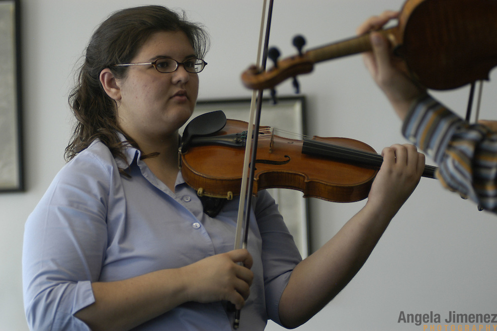 """Violinist Elizabeth """"Libby"""" Fayette of Long Island, New York, 17, left, gets adjustments from teacher Kyu-Young Kim (a substitute instructor who is not her regular teacher) during her weekly private lesson in the Pre-College Division program at The Juilliard School, located at West 65th Street and Broadway in New York City, on Saturday, September 24, 2005. Students audition for spots in the prestigious program, in which they can study until they graduate from high school."""